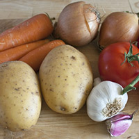 Some carrots, potatoes, onions, tomatoes, garlic and laurel on chopping board.