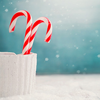 Christmas background. Candy canes on snow. Xmas decoration
